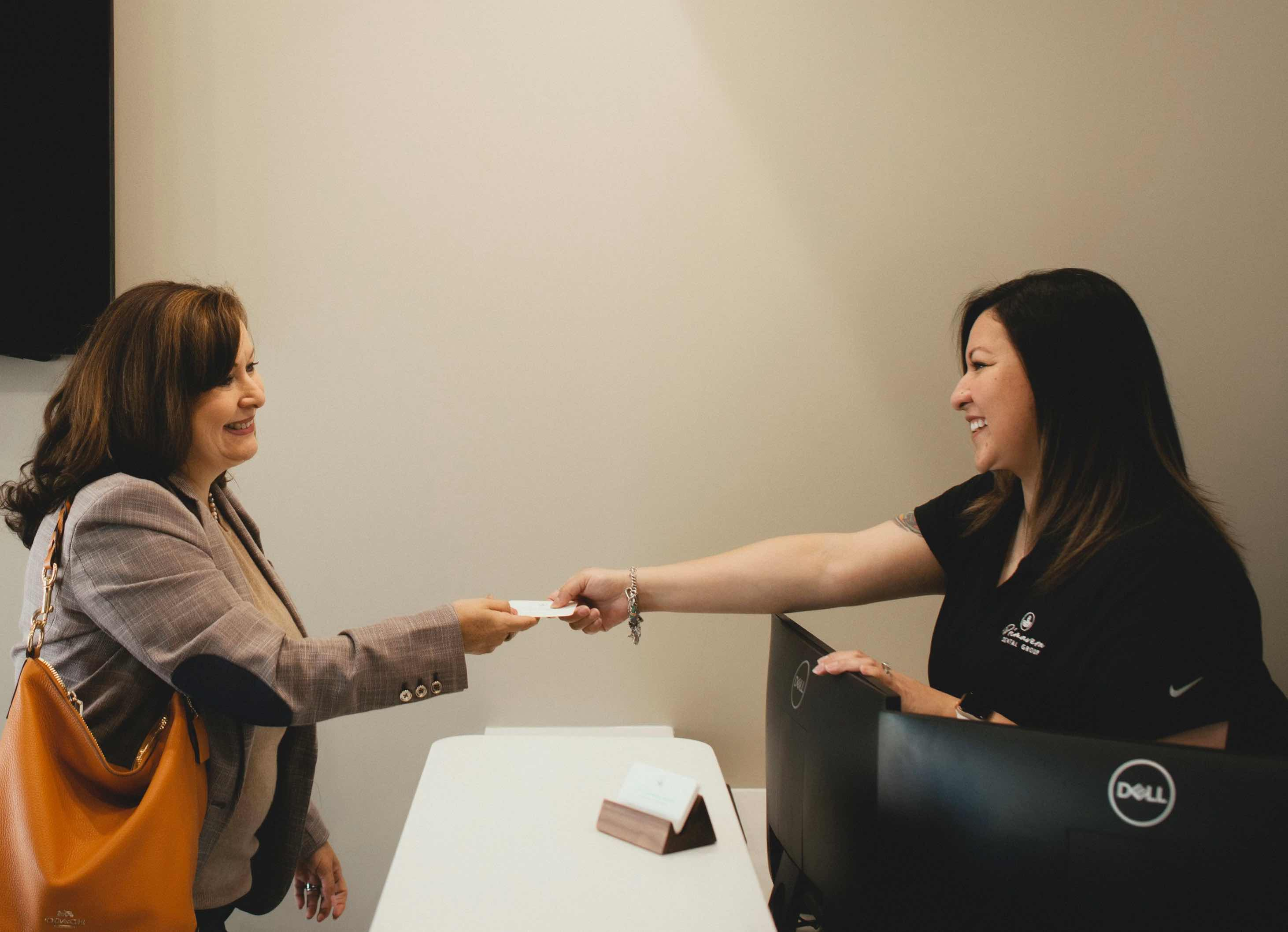 Photo of a team member passing a business card to a patient over a counter