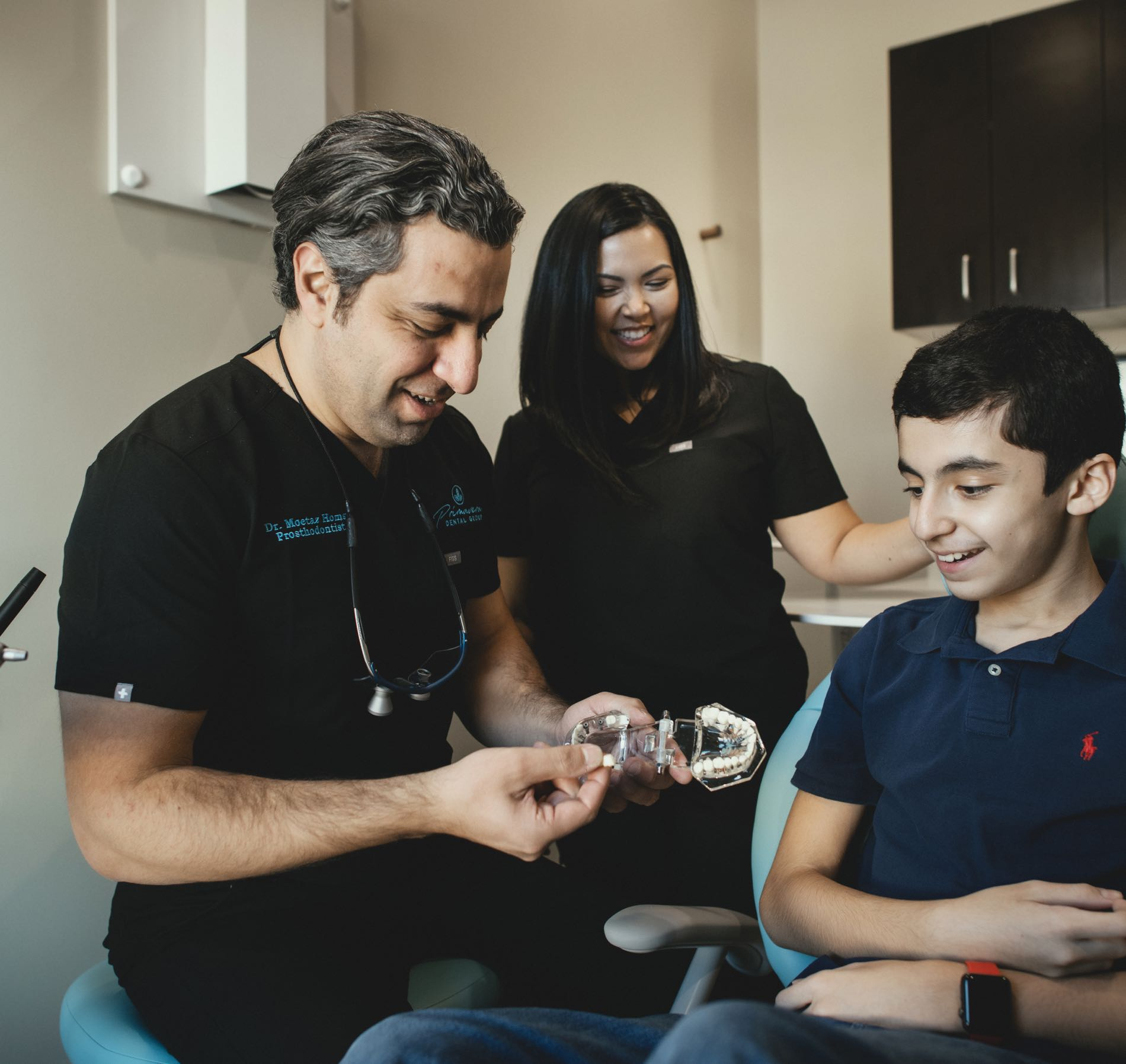 Photo of Pflugerville dentist Dr. Moetaz Homsi showing a dental model to a teenage patient