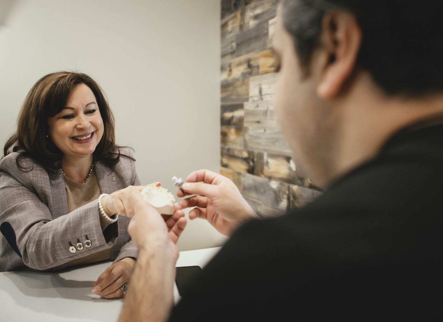 Photo of a patient looking at a dental implant model