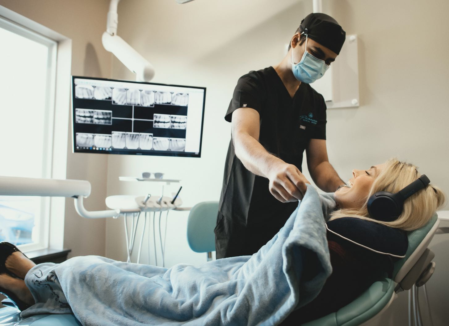 Photo of a team member putting a blanket on a smiling relaxed patient laying in a dental chair