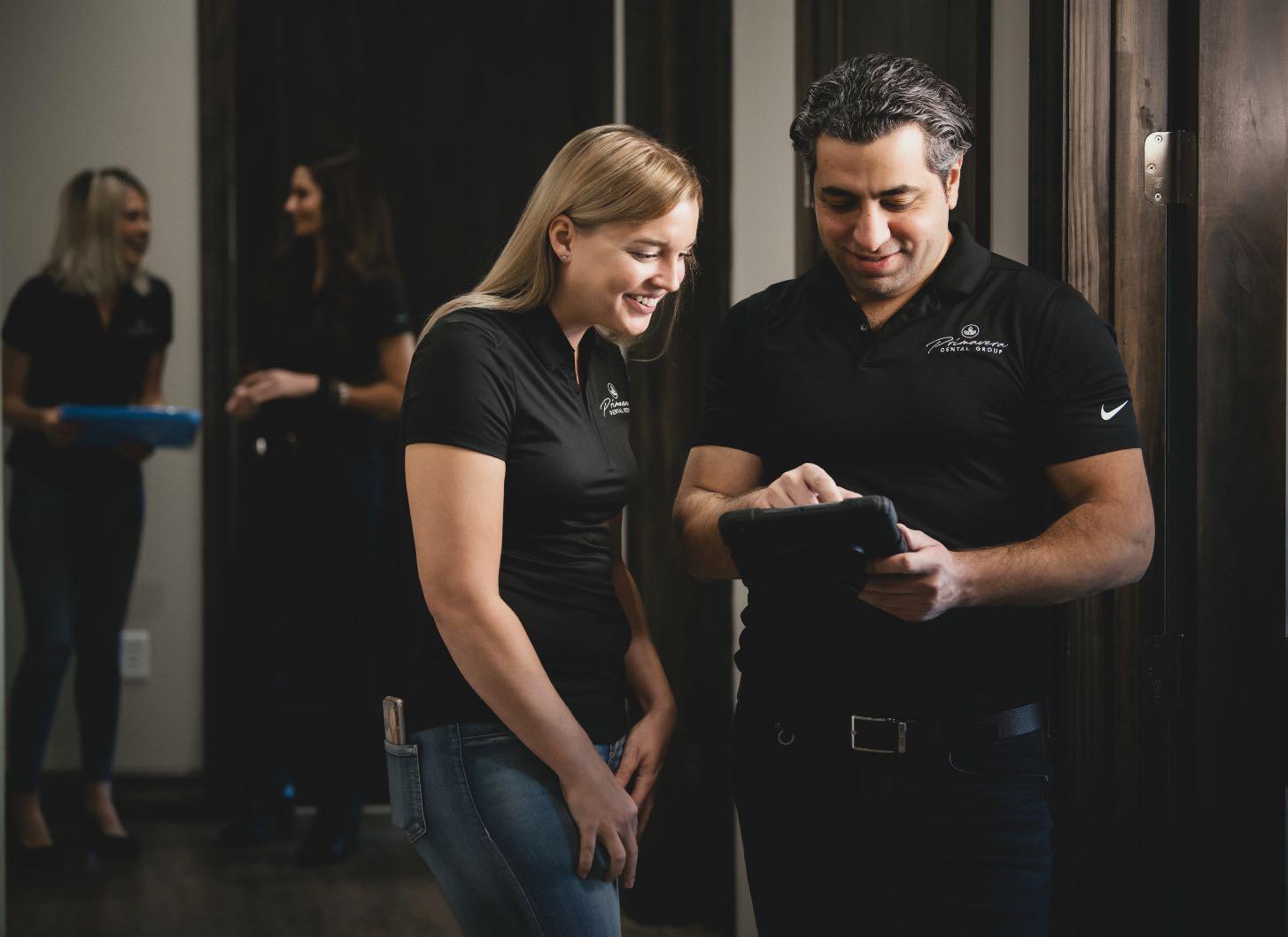 Photo of Dr. Homsi and a dental team member looking at an iPad