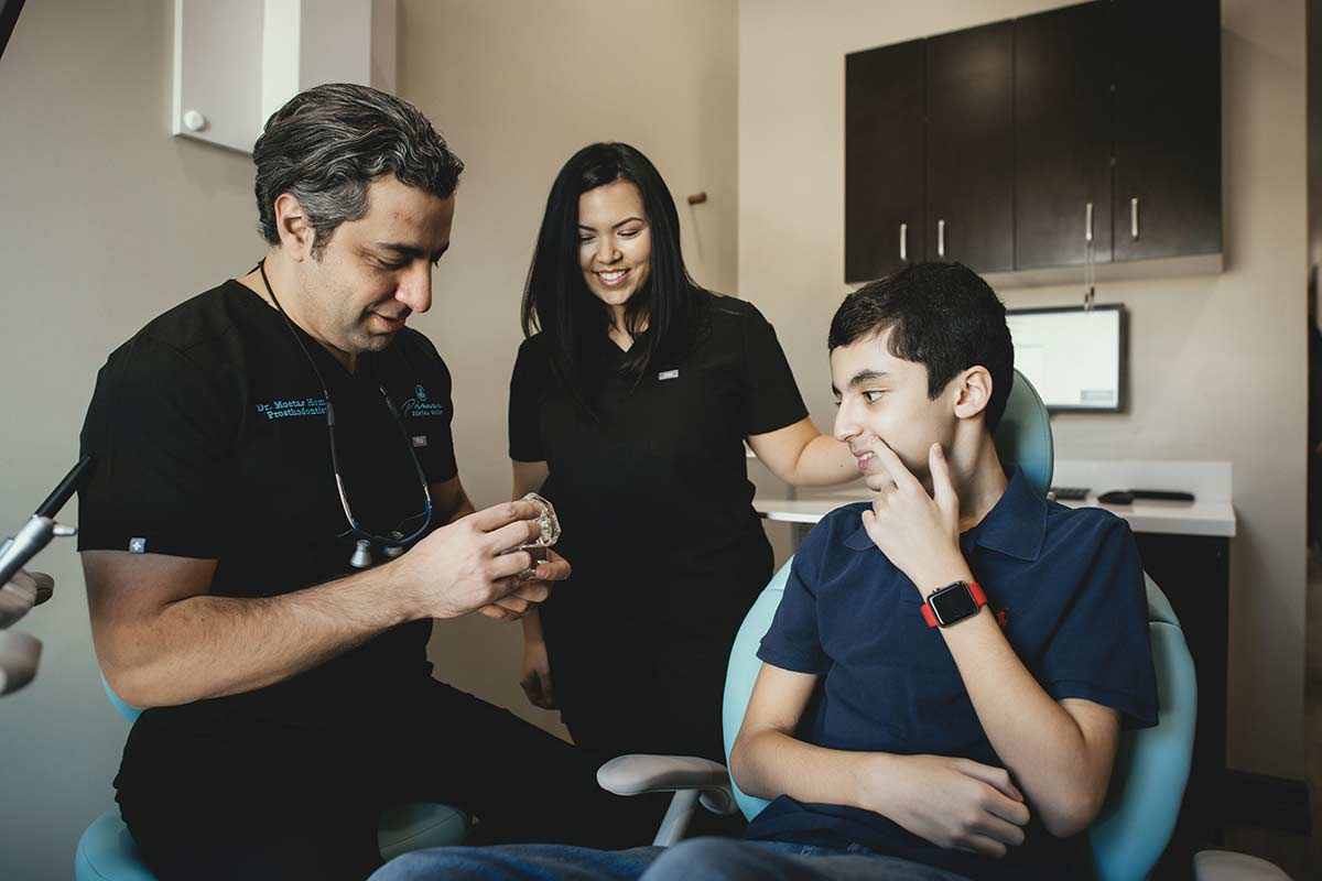 Photo of Dr. Homsi talking with a young patient and a team member