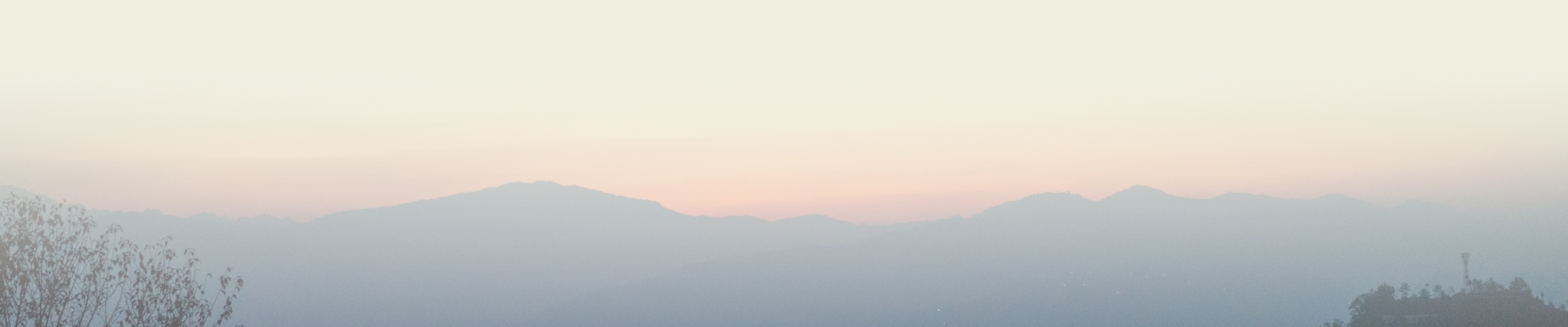 a soft pink and orange sunset behind a mountain range.
