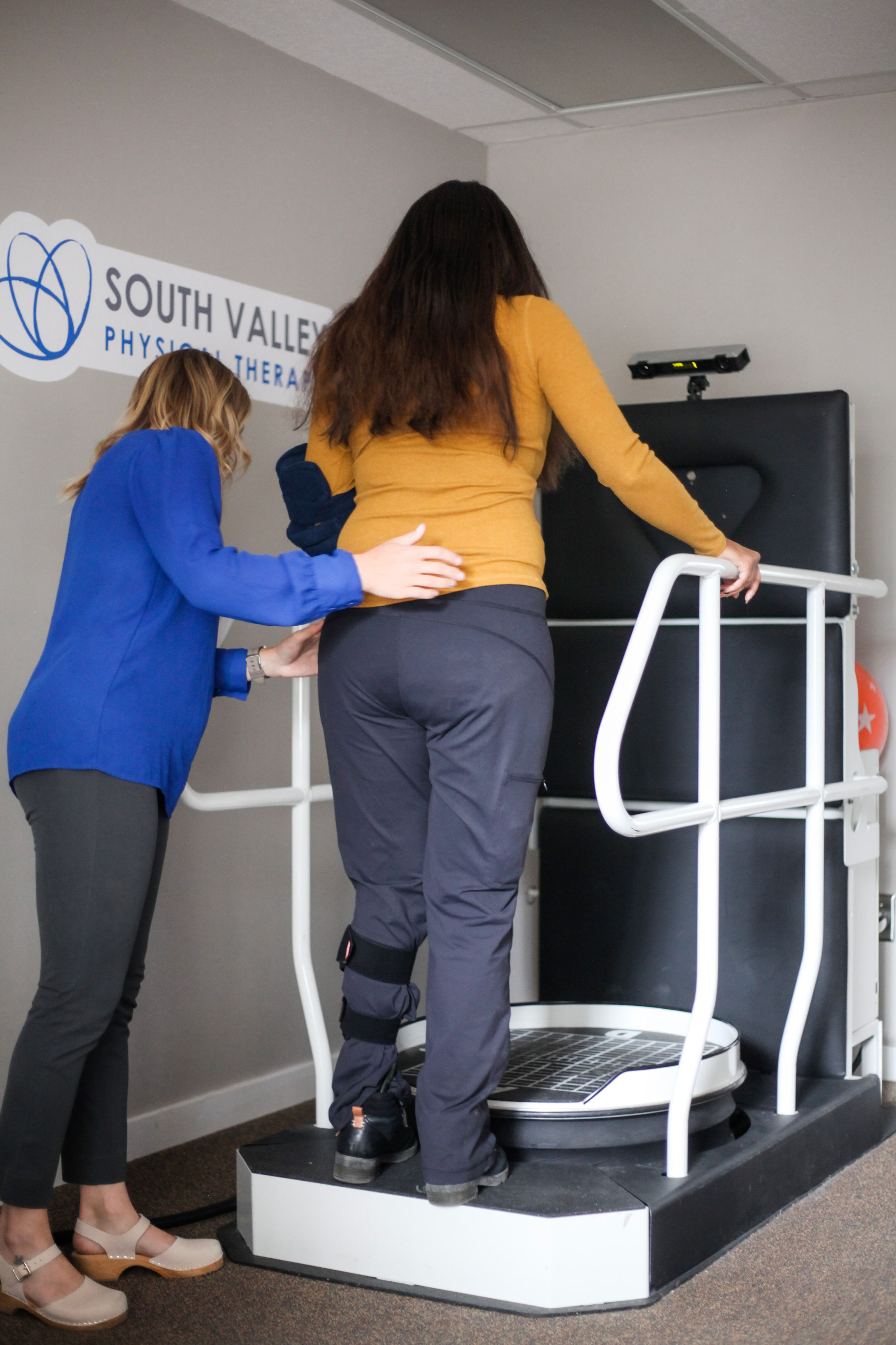 A woman stepping up to a balance machine.
