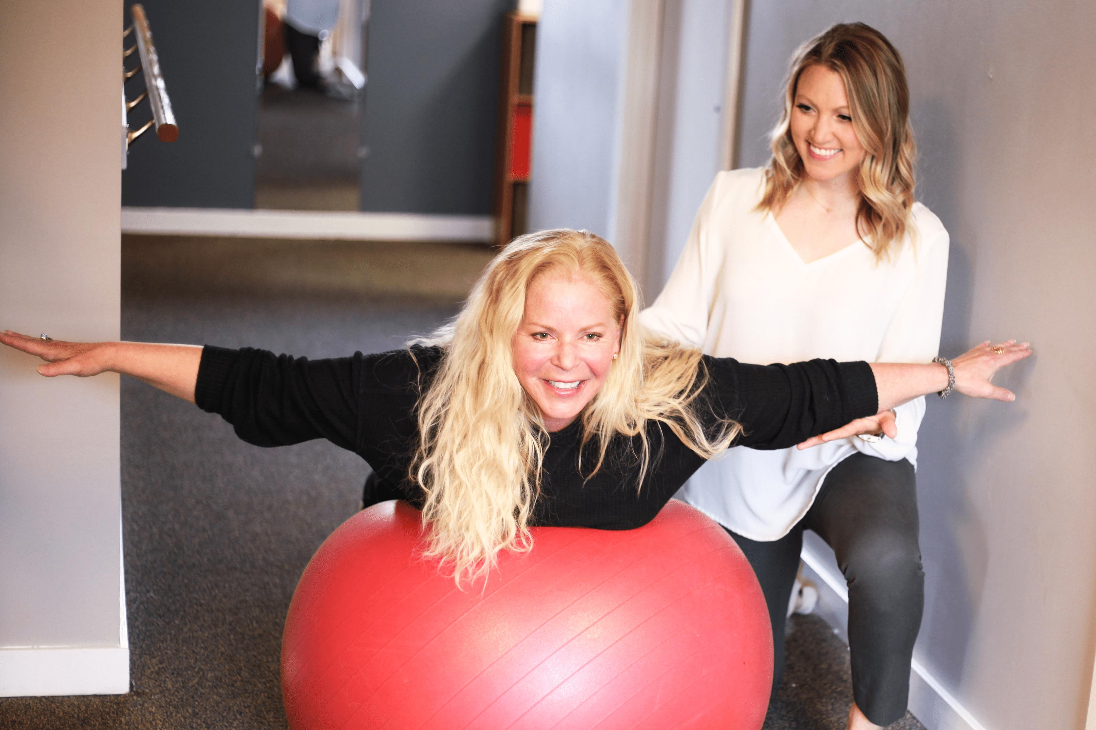 A woman balancing on a ball.