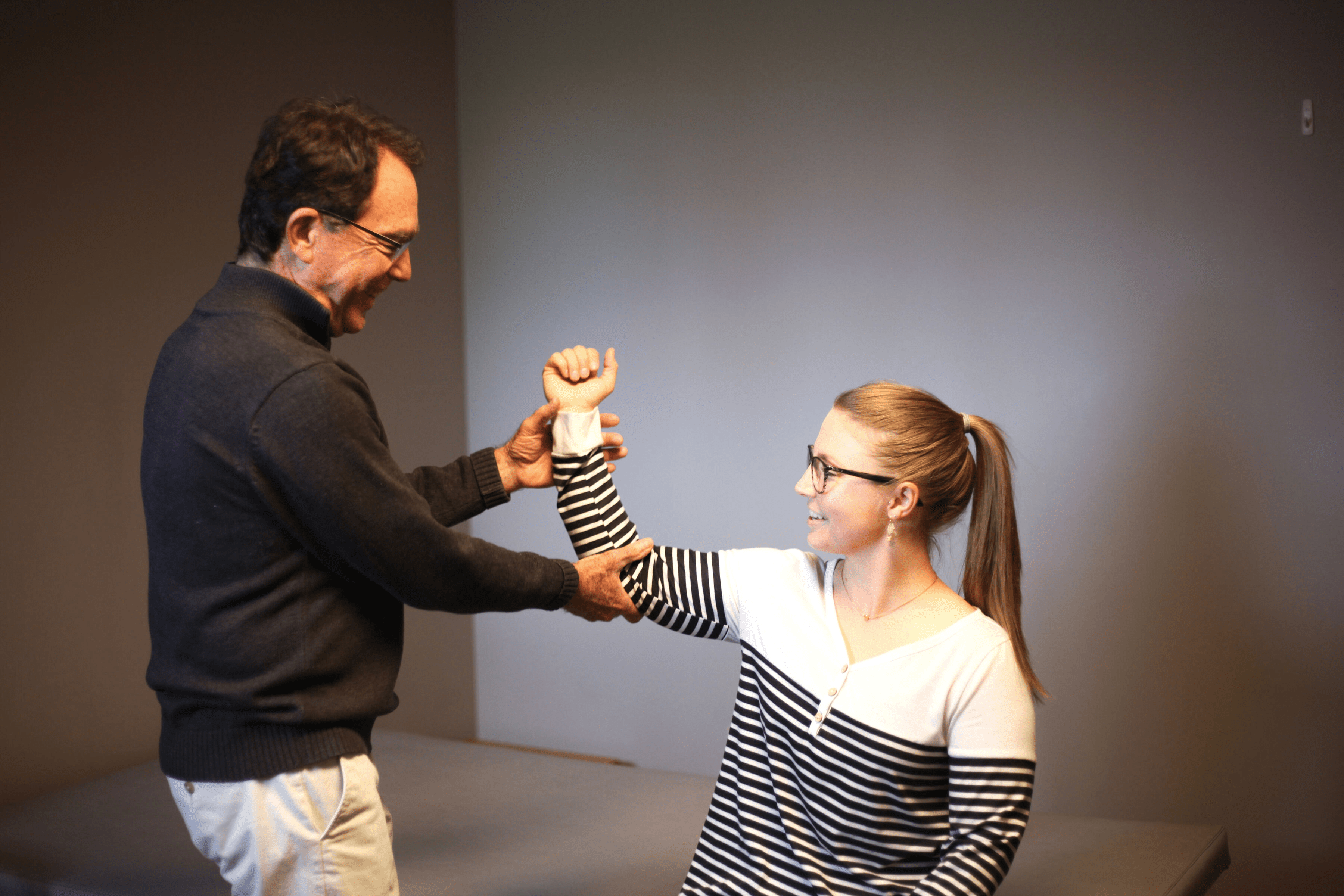 A physical therapy testing a patient's arm movement.
