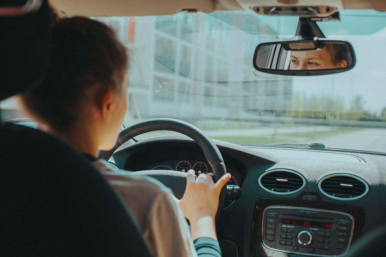 Bild einer Frau am Steuer in einem Auto.