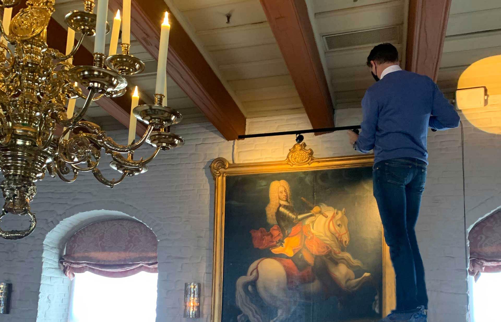 En mann justerer lyset over et maleri