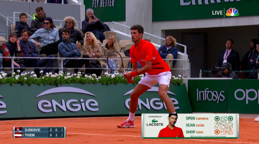 Djokovic playing a tennis match on TV with a Lacoste QR code advert at the bottom corner of the screen