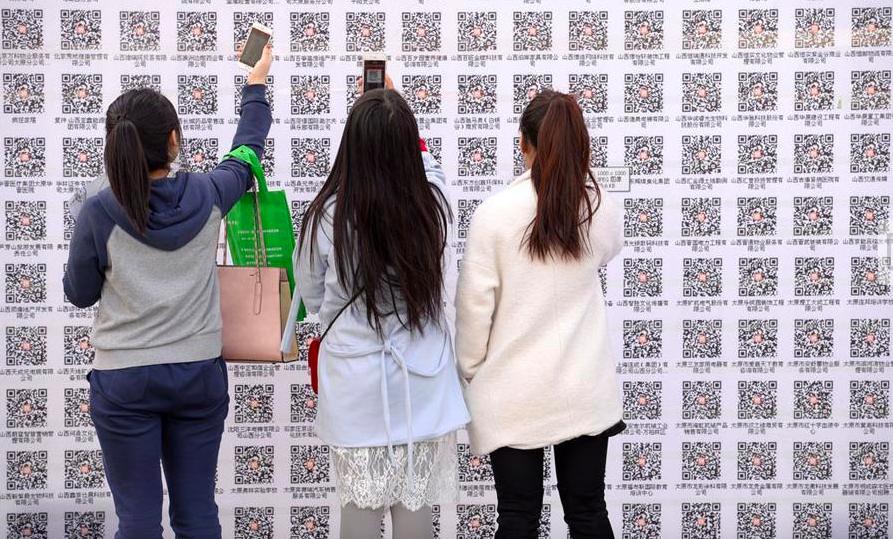 girls scanning qr codes on wall at a job fair