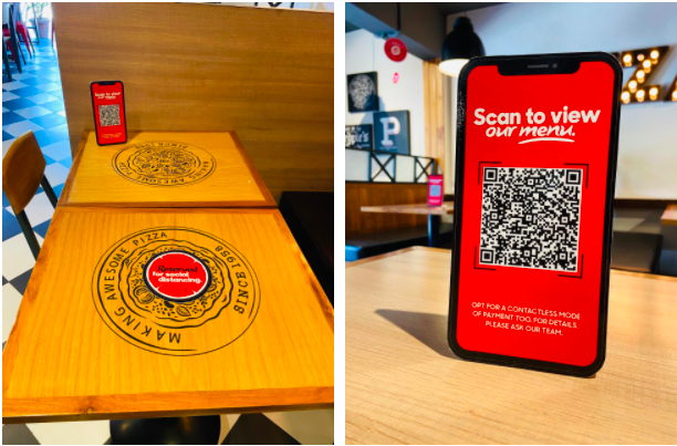 a large qr code on a phone to scan for menu at a pizza restaurant