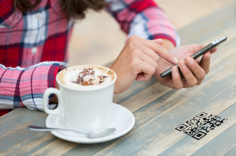a person taking qr code photo on the coffee table