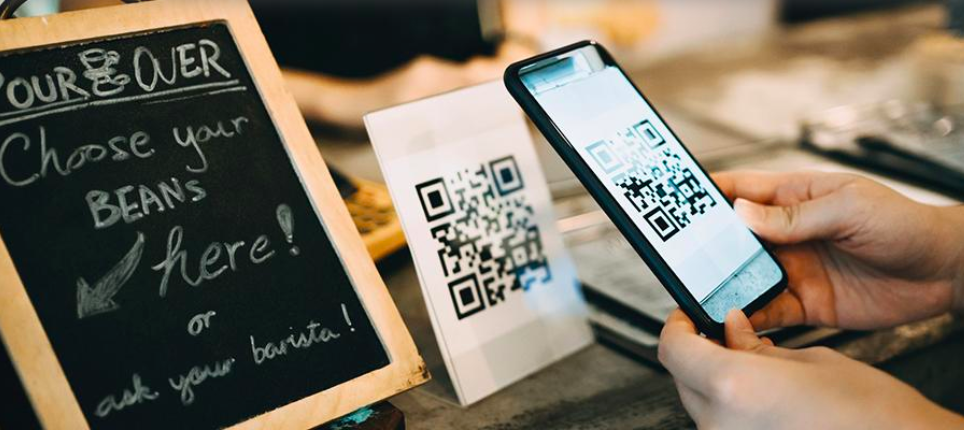 Hands scanning a QR code on their mobile at a coffee shop register