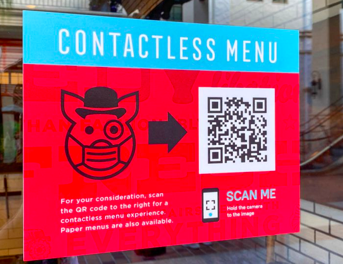 A contactless QR code menu poster on the window