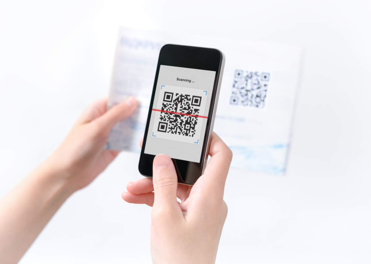 Hands scanning a QR code from a document