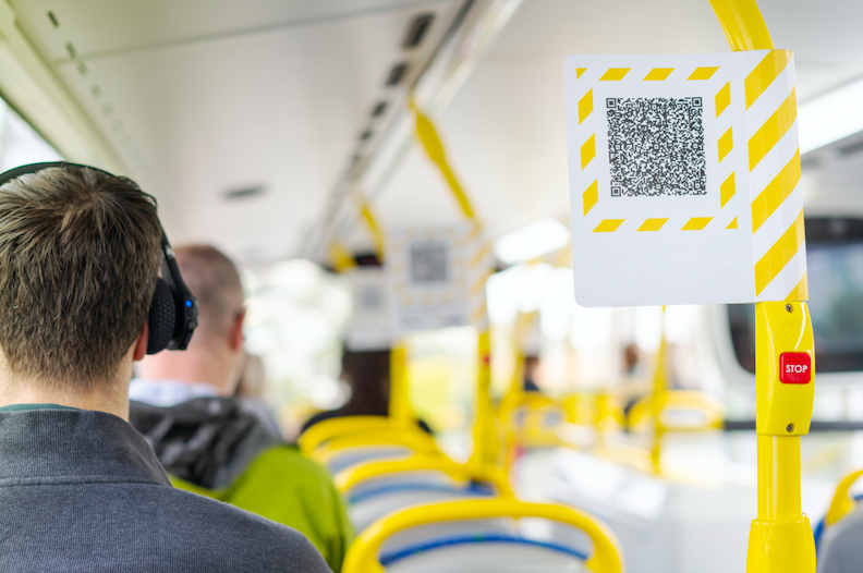 QR code on bus with a guy listening to headphones