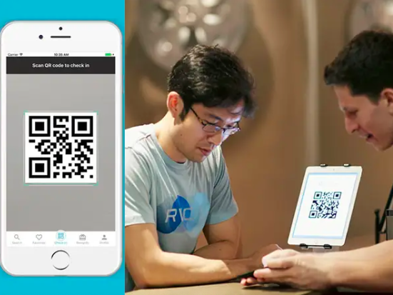two guys at the check-in counter at the gym with a QR code