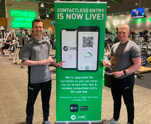 two guys standing next to a banner with a qr code app for contactless entry to jd gyms