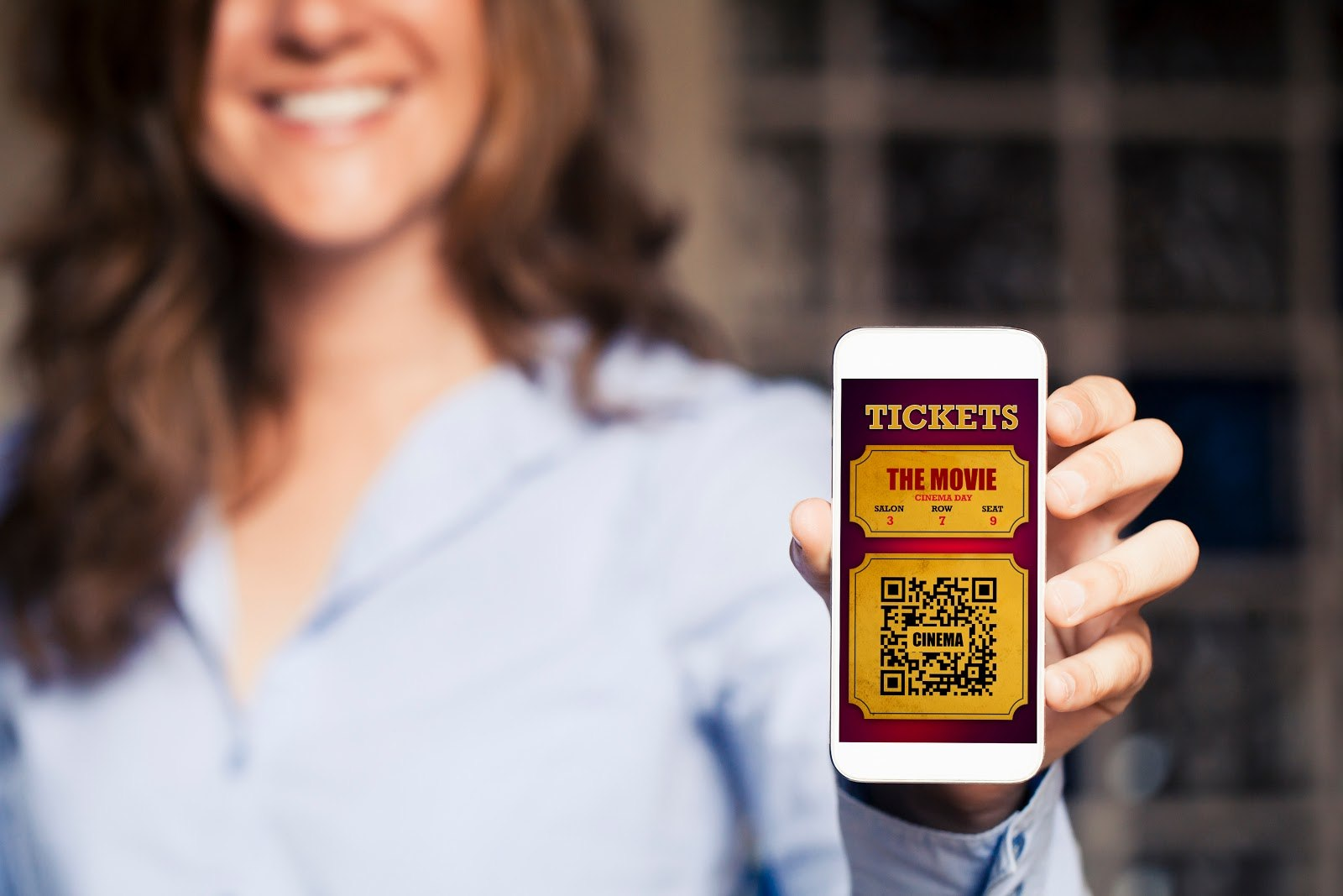 A woman holding a phone with a QR code ticket to the movie