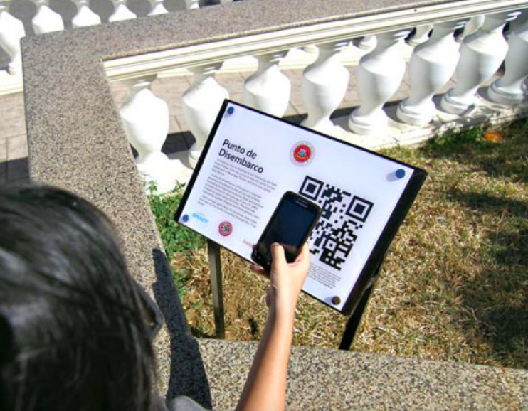 girl scans QR code on public park sign