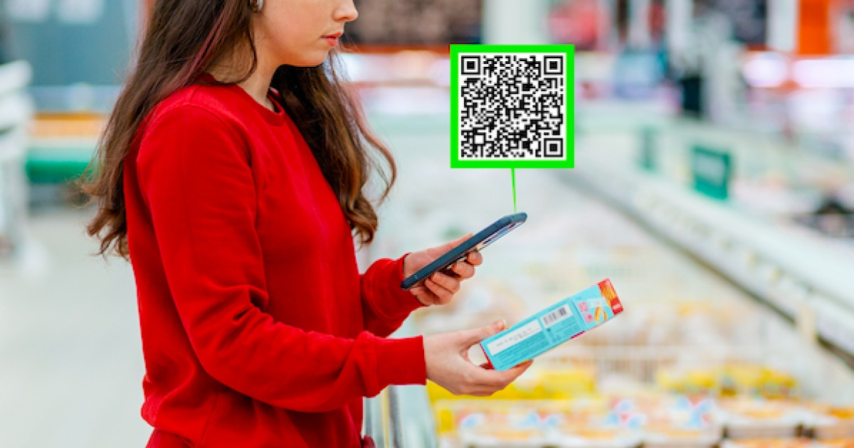 a woman scanning a qr code on food packing in a supermarket