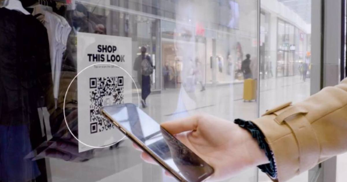 phone scanning a qr code in window to shop the look
