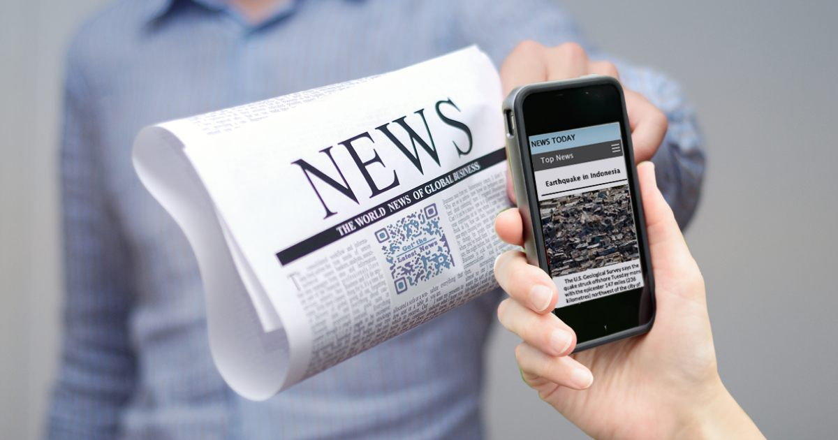 phone scanning a qr code in news section of the newspaper