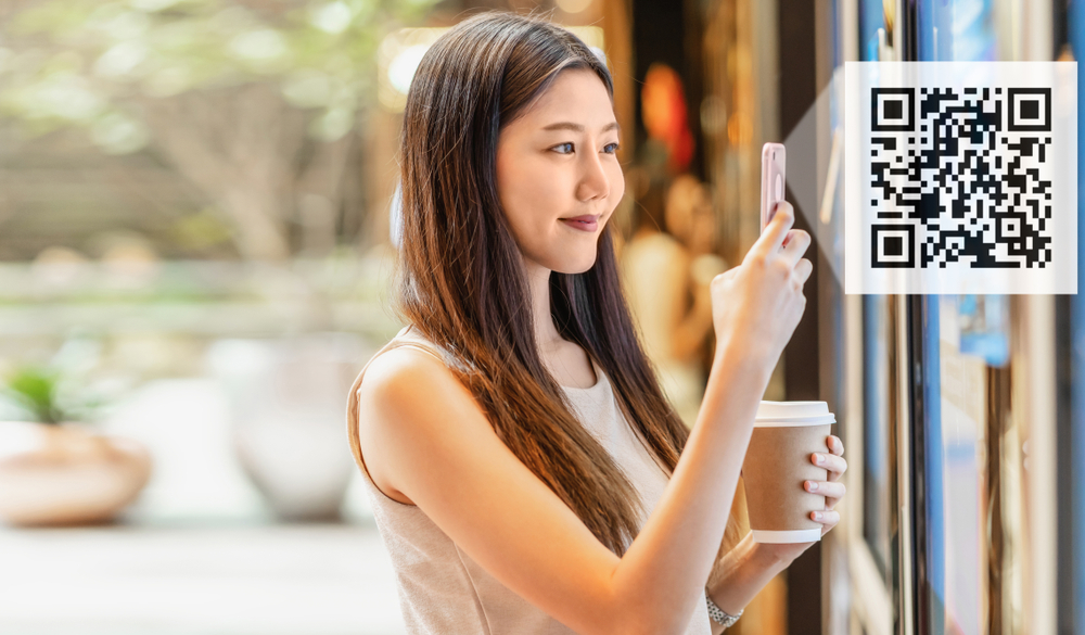 Asian woman scanning a QR code
