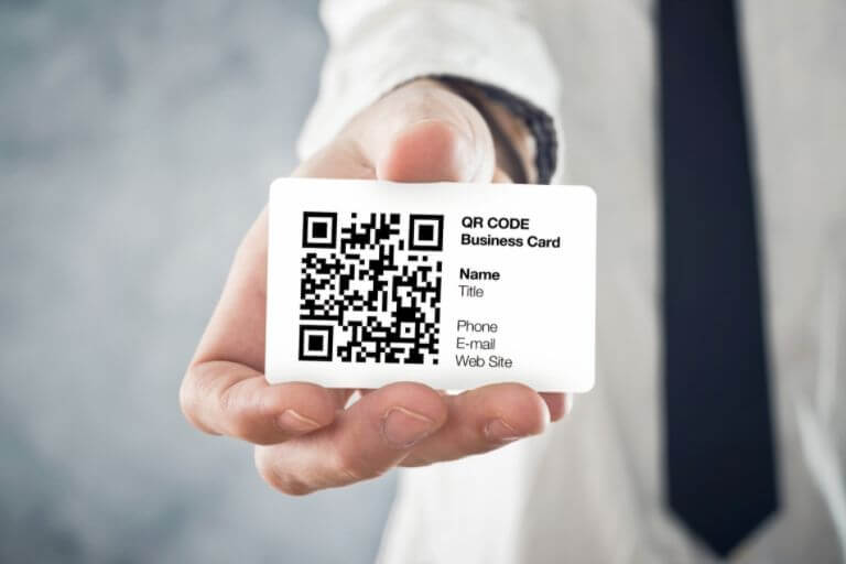 a man in a tie showing printed qr code on his business card
