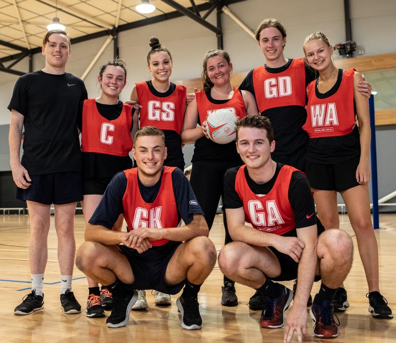 Mixed netball team wearing red bibs