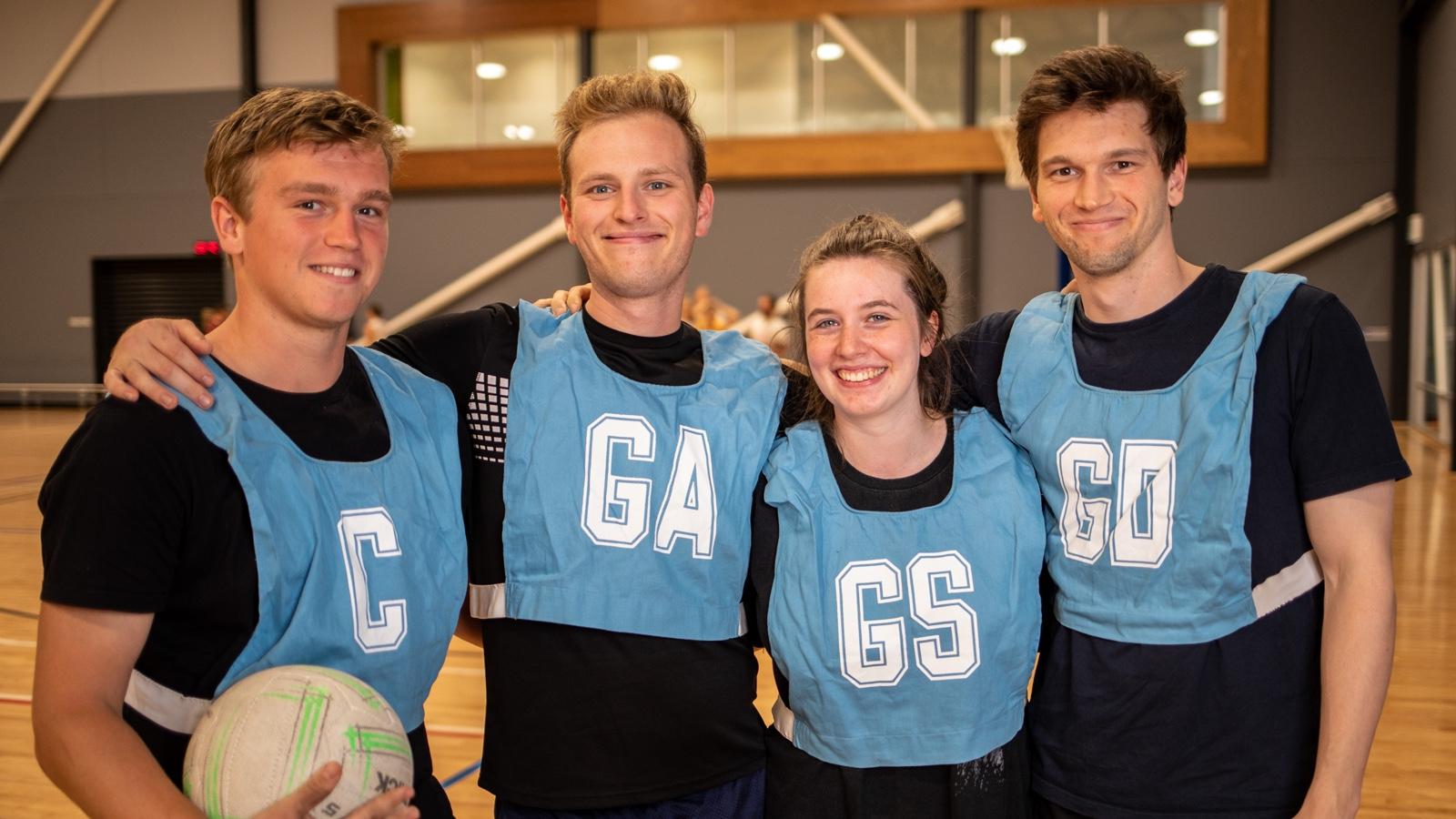 Mixed netball team wearing blue bibs