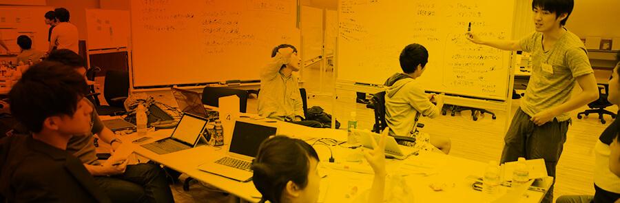 ホワイトボードに書かれた事業案を検討する学生達