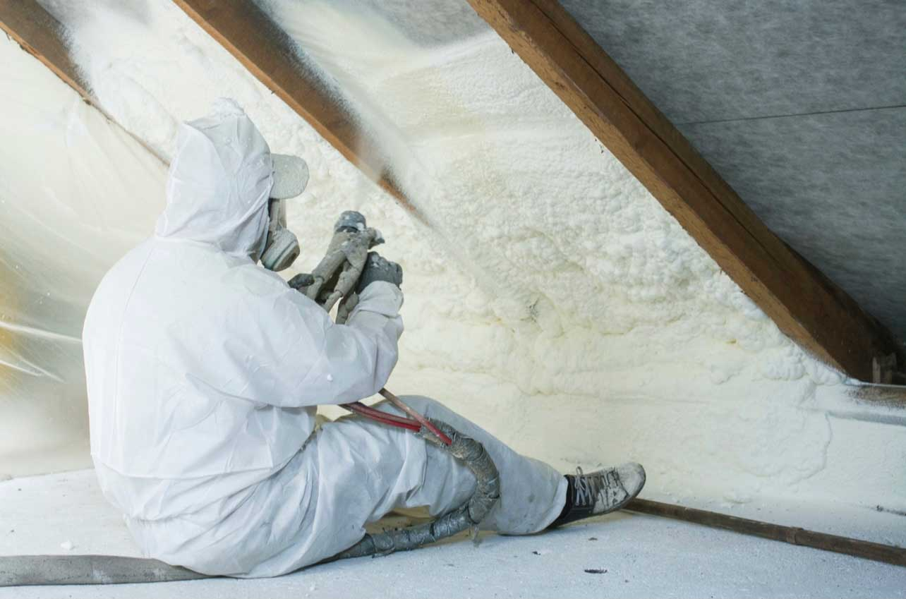 person in full protective clothing and mask spraying foam to insulate a loft