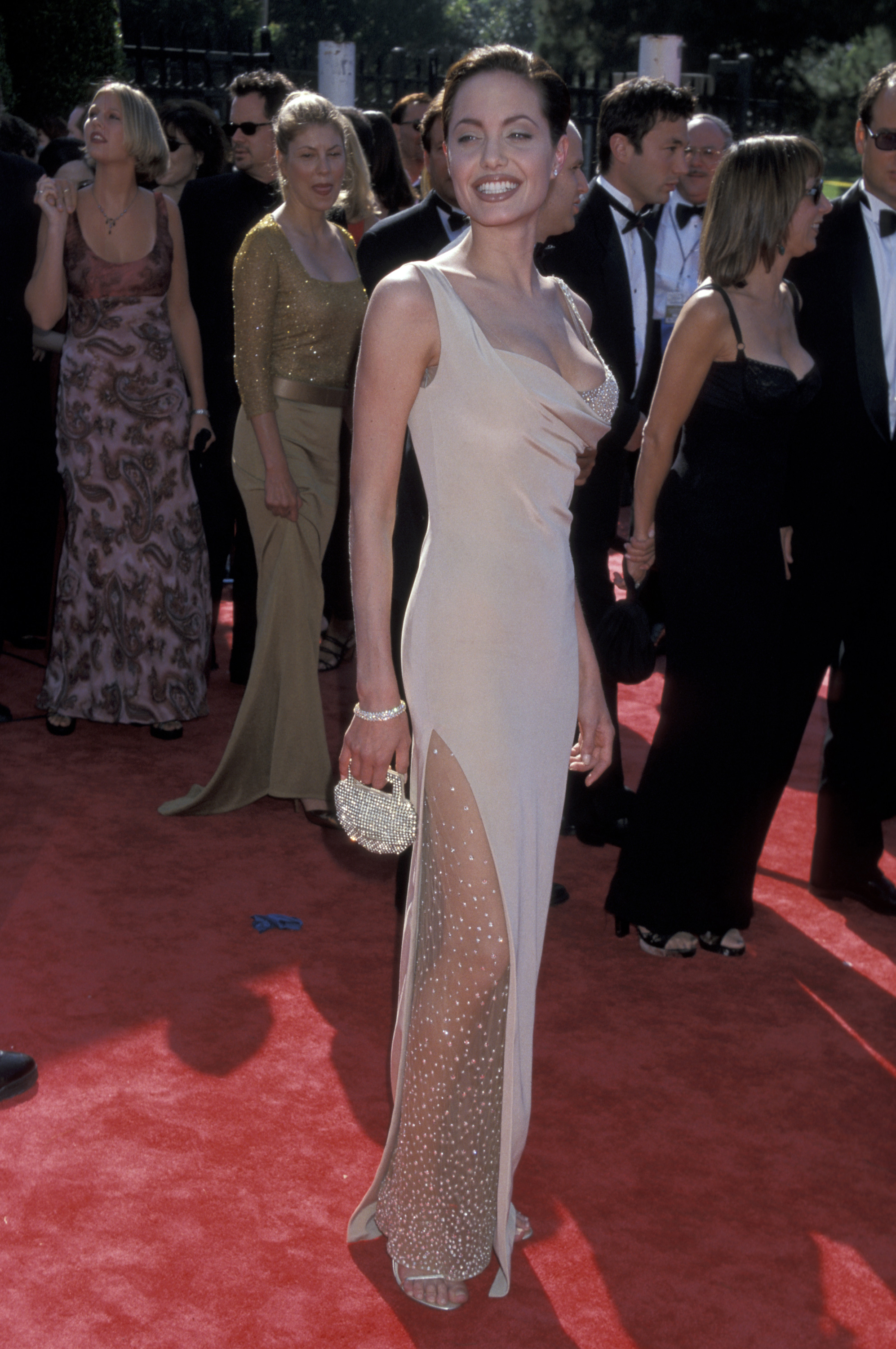 angelina jolie smiling on the red carpet wearing a slit dress