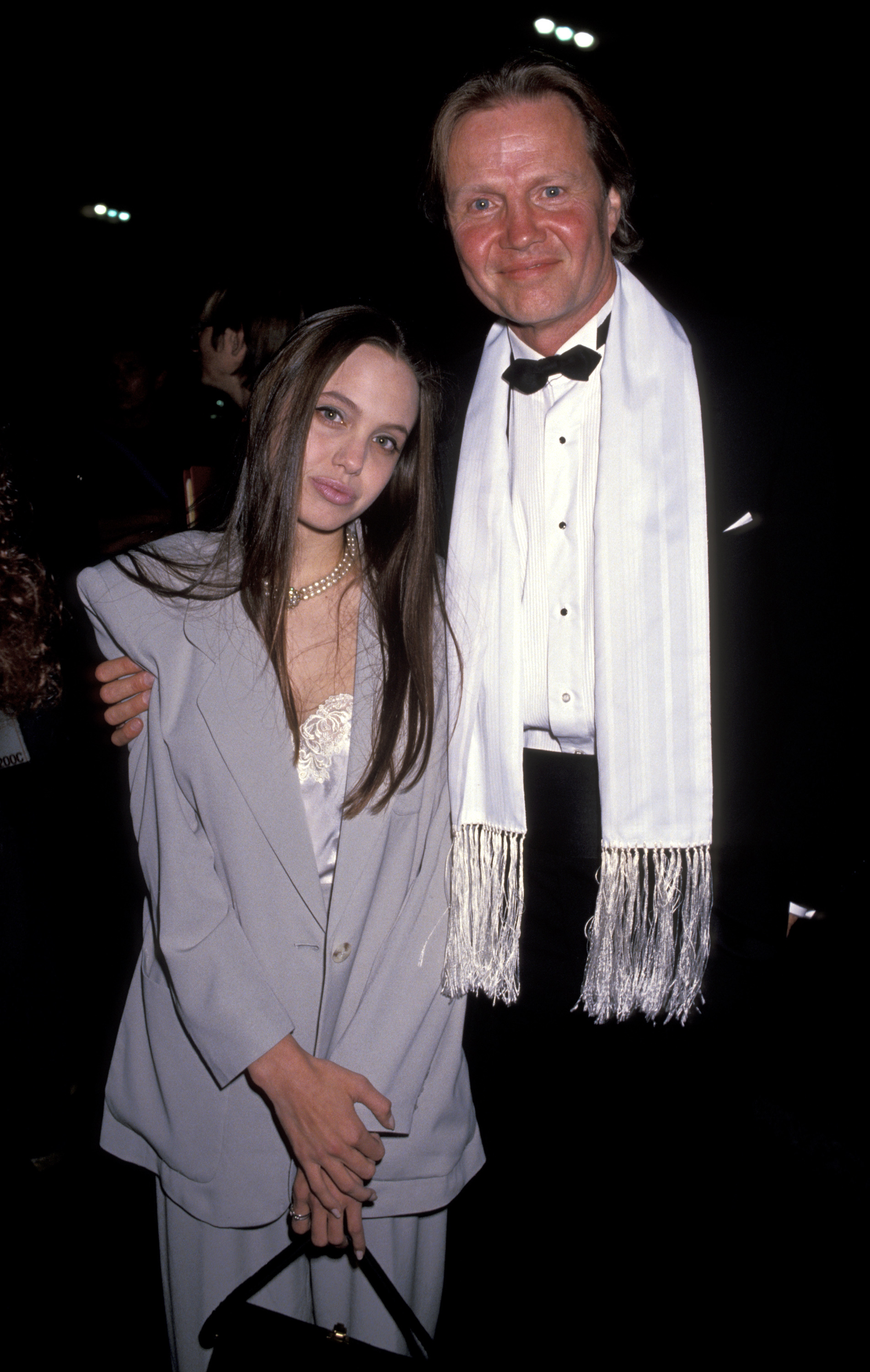 jon voigt with his arm around angelina jolie on the red carpet