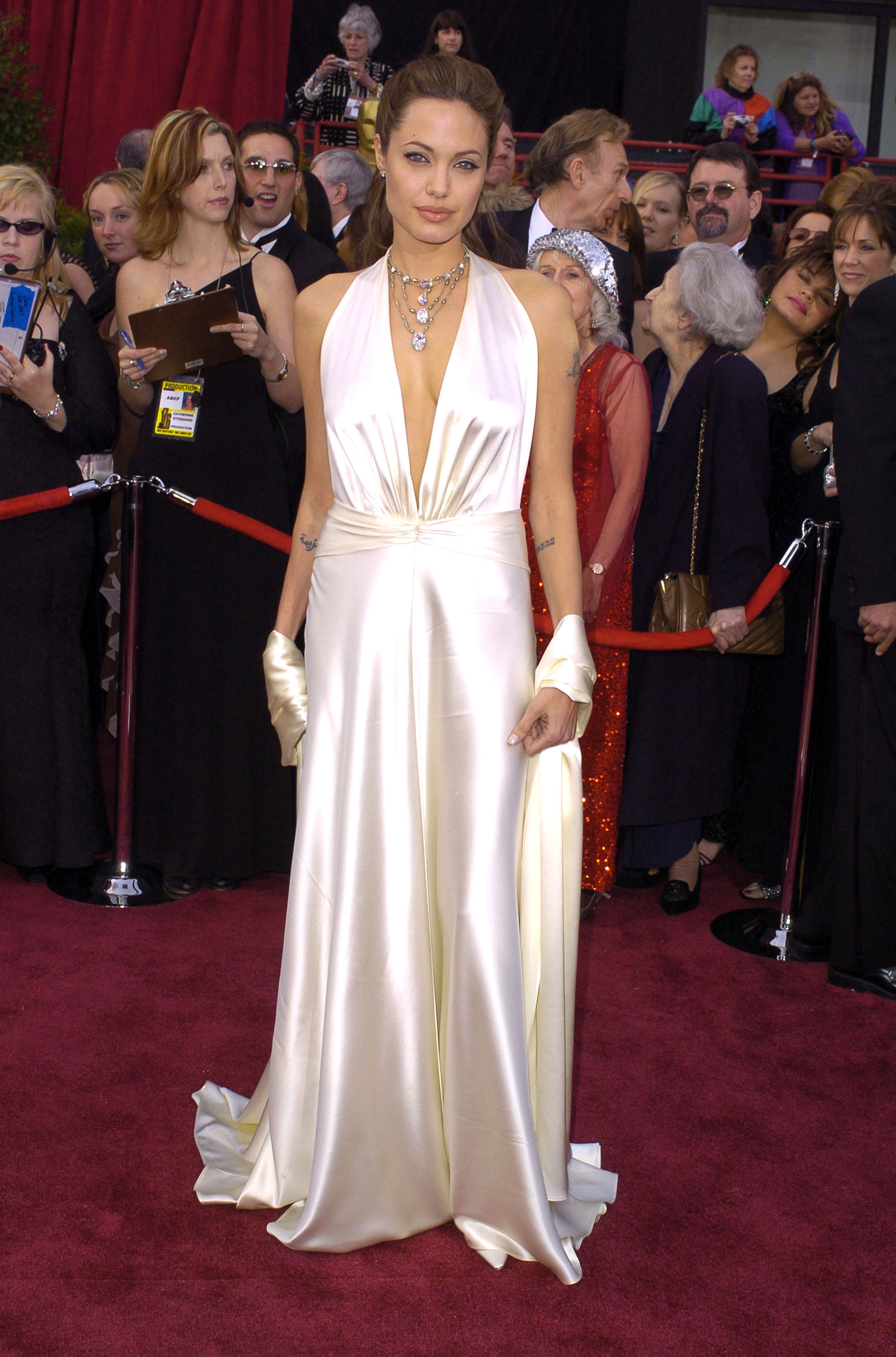 angelina jolie posing on the red carpet in a white silk dress