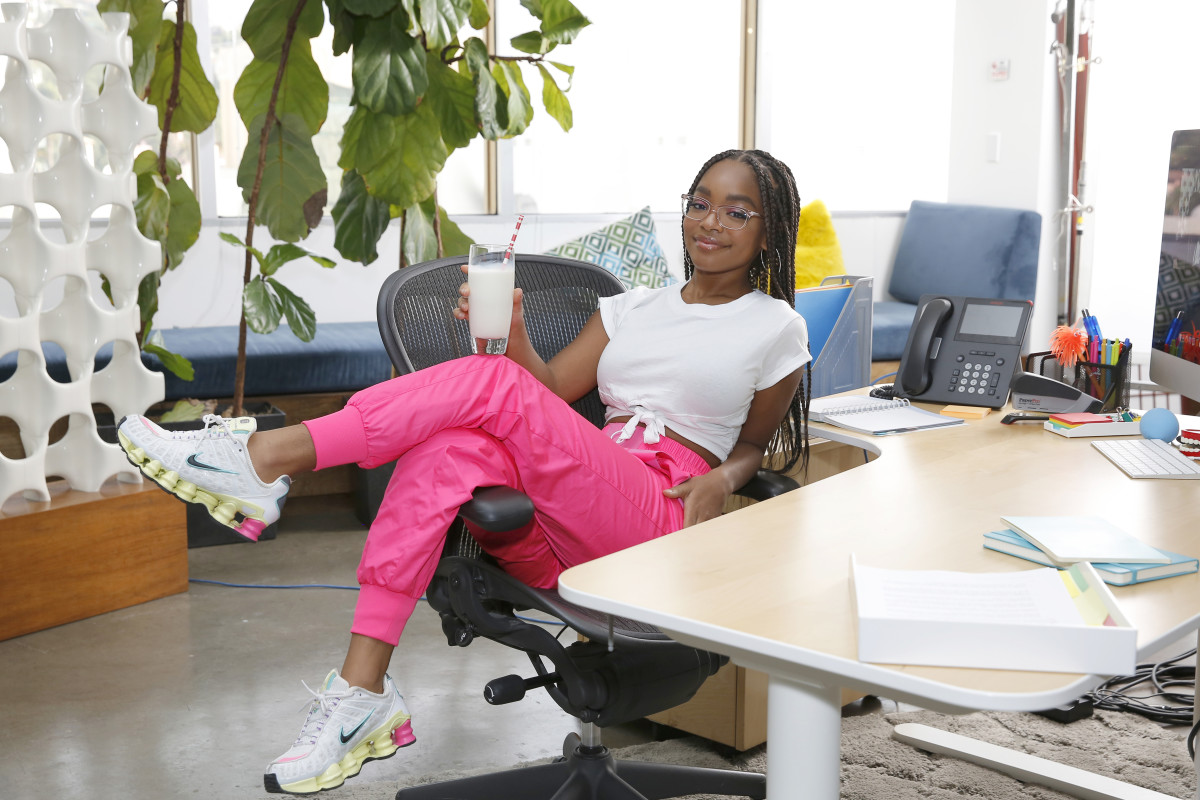 Wearing a white tee with pink track pants and Nike sneakers.