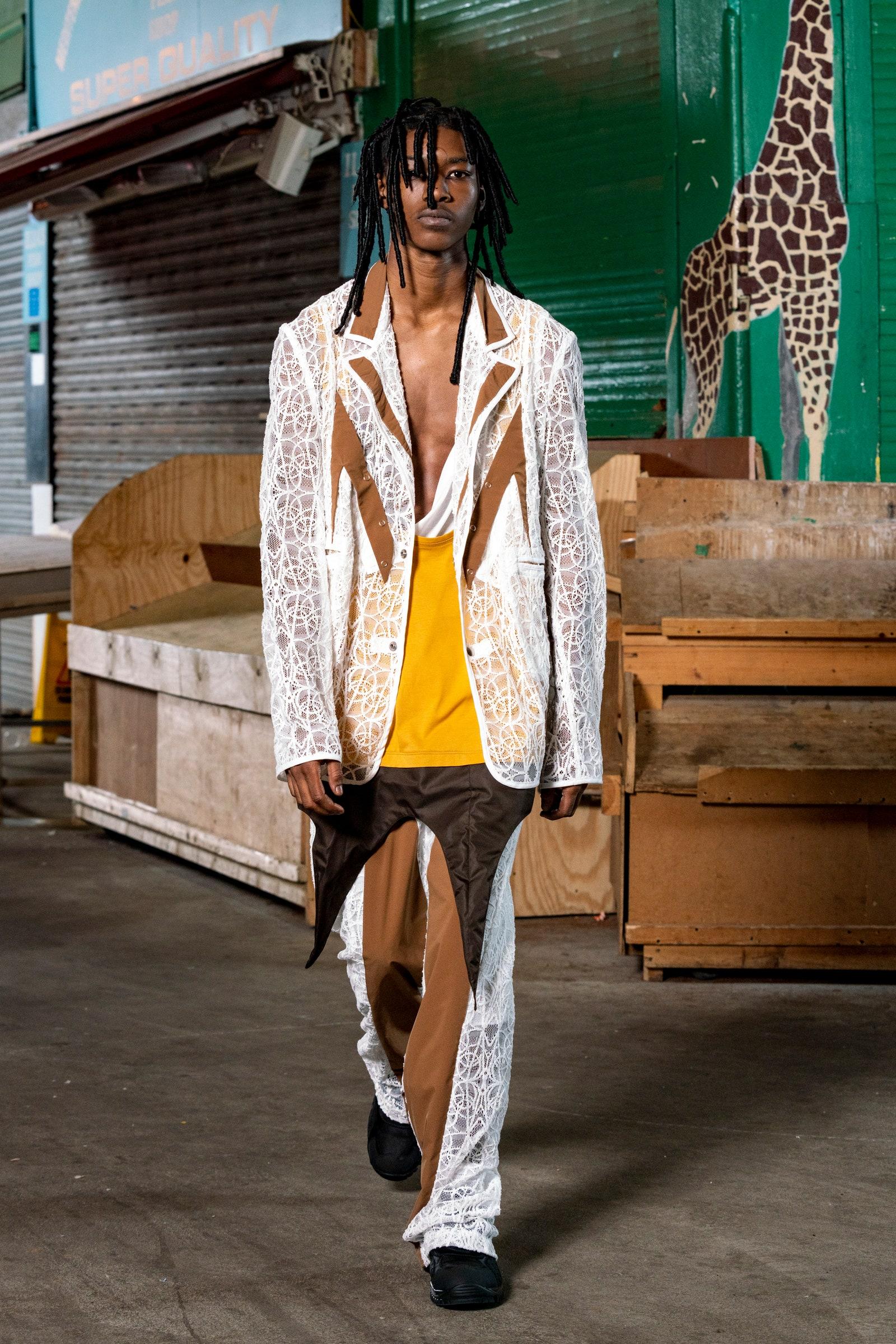 Image may contain Clothing Apparel Sleeve Wood Human Person Long Sleeve Animal Wildlife Mammal and Giraffe
