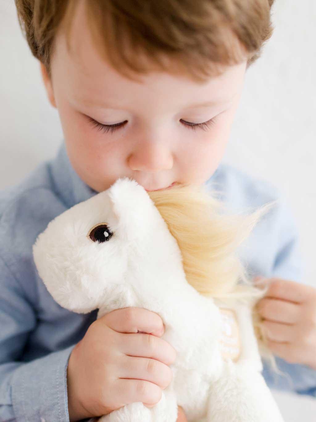 Young boy holding a white mini Piccoli horse toy