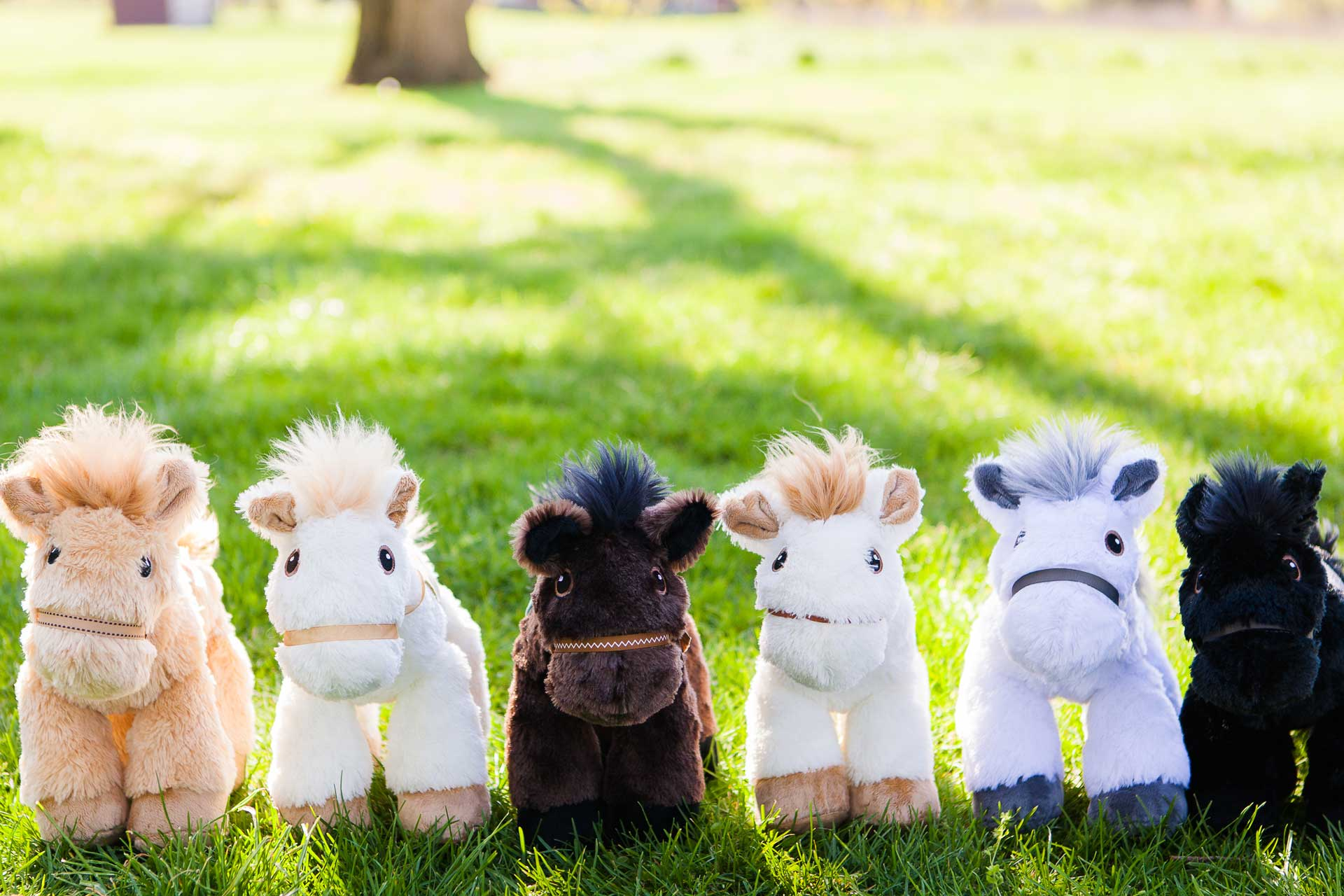 Piccoli Plush horses lined up in the springtime grass.