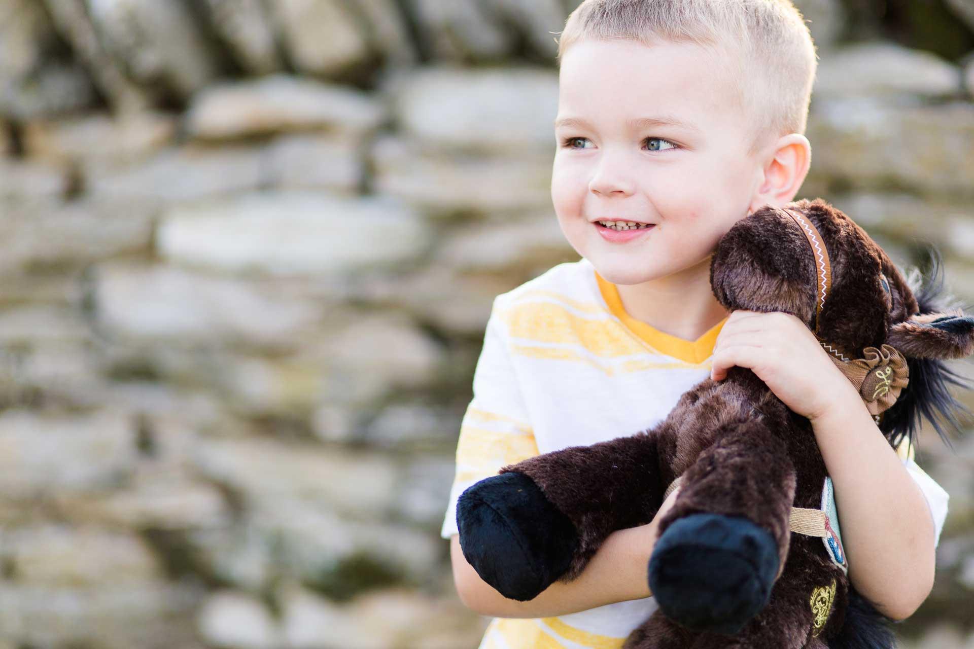 Boy hugging brown plush horse