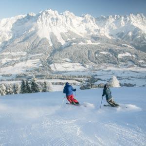 2 Skifahrer ziehen kurze Schwünge in die frisch präparierte Pulverschneepiste. Im Hintergrund strahlt der Wilde Kaiser in prachtvollem Winterkleid.