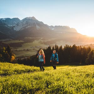 2 Wanderer schreiten entlang eines Wiesenpfades. Im Hintergrund das Bergmassiv des Wilden Kaisers.