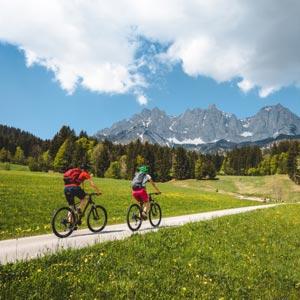 2 Radfahrer auf einem abgelegenen Radweg mitten in der Natur. Im Hintergrund das Bergmassiv des Wilden Kaisers.