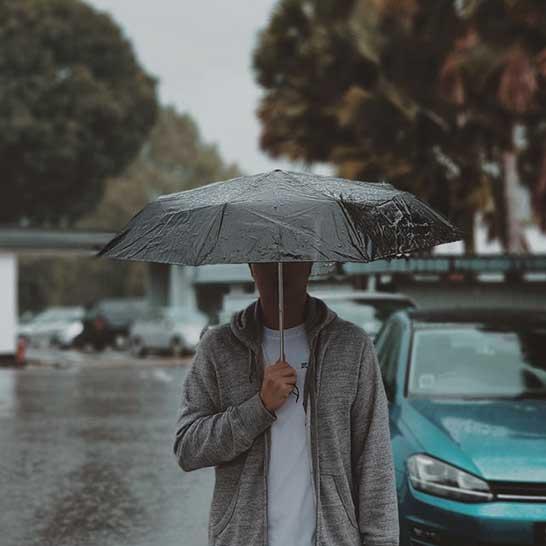 Mann im Regen mit schwarzem Regenschirm