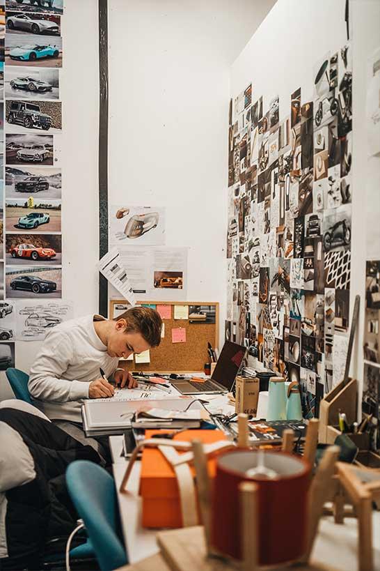 Mann, der etwas notiert, an überfülltem Schreibtisch
