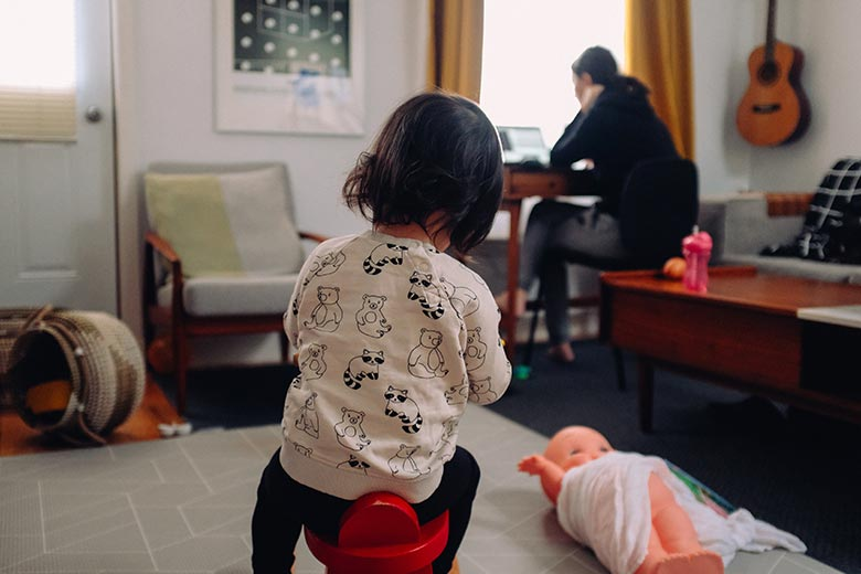 Spielendes Kind von hinten und Mutter an Schreibtisch