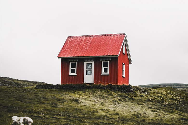 Rotes Holzhaus auf Grashügel