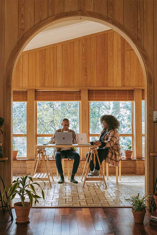Mann und Frau an einem Holzschreibtisch vor Laptop