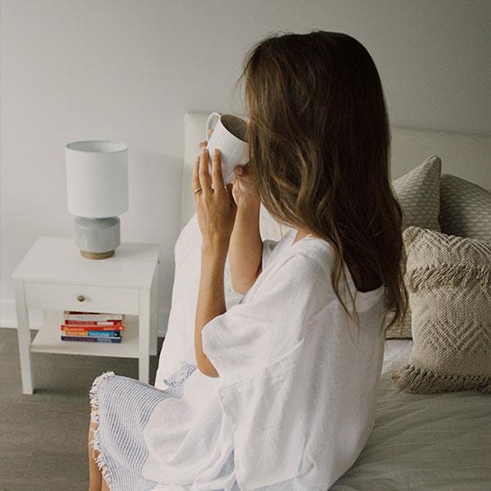 Auf Bett sitzende Frau in weißem Nachthemd, die aus Tasse trinkt